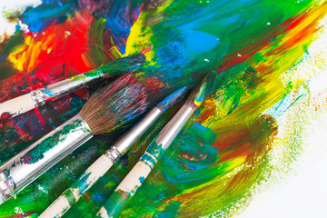 Brushes and paints artist on an abstract background