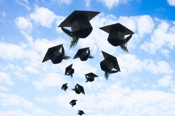 Graduation day, Images of graduation Caps or hat throwing in the air with sunshine day on blue sky background, Happiness feeling, Commencement day, Congratulation, Ceremony