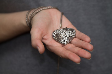 a steel heart in woman's hands as a symbol of love