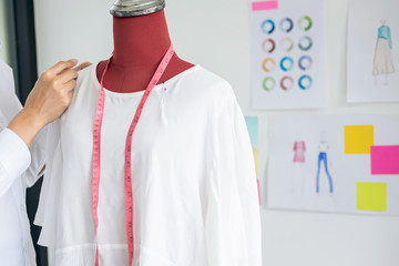 Young woman dressmaker or designer working as measuring for clothes as red dummy, profession and job occupation, Designer Stylish Concept