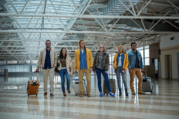 Positive team. Full length portrait of cheerful young friends are standing with luggage at terminal hall and looking at camera with smile while waiting for departure