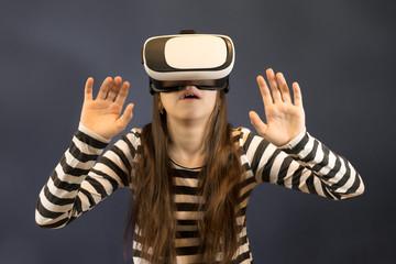 Shocked teenager girl using virtual reality device in studio.