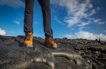 Female legs in black pants and yellow hiking boots standing on black lava