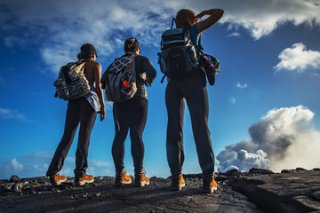 A group of three girls wearing trekking shoes standing on black lava field