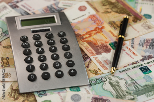 Calculator And Pen Lying On The Background Of Money