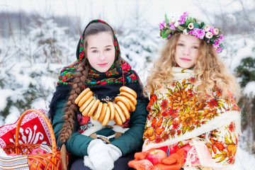 Girls in Russian national clothes in the winter landscape