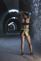 Stretching beauty woman in tunnel after running