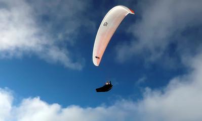 A paraglider flies above the Alps near Lenzerheide