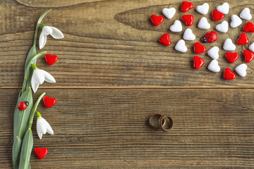 Valentines day concept of red and white hearts with two wooden wedding rings symbolize endless love of two persons decorated with fresh snowdrops on wooden vintage background.