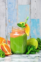 Fresh Green Smoothies with blood oranges. Green smoothie jar on the light background