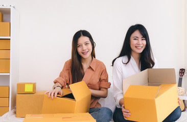 Freelancer asian women teamwork sme business working at office in home interior packing order for customer and online delivery for ready packing on living room