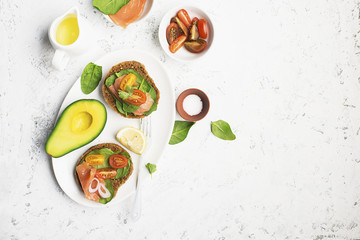 Healthy breakfast: cereal rolls with salmon, cherry tomatoes, spinach, avocado. blueberry on a light background. Top view. Copy space.