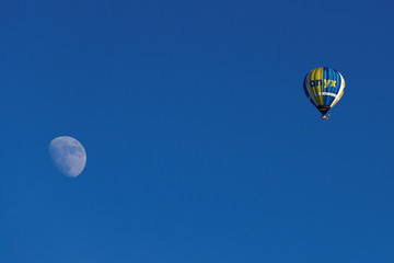 A balloon flies, with the moon in the background, during the International Hot Air Balloon Week in Chateau-d'Oex