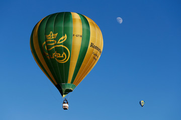 Balloons fly, with the moon in the background, during the International Hot Air Balloon Week in Chateau-d'Oex