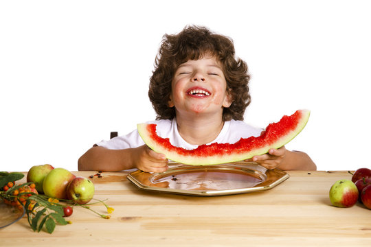Small happy little boy covering his eyes with pleasure eat delicious ripe watermelon. White background. Close-up.