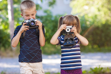 Two children with photo cameras outdoors