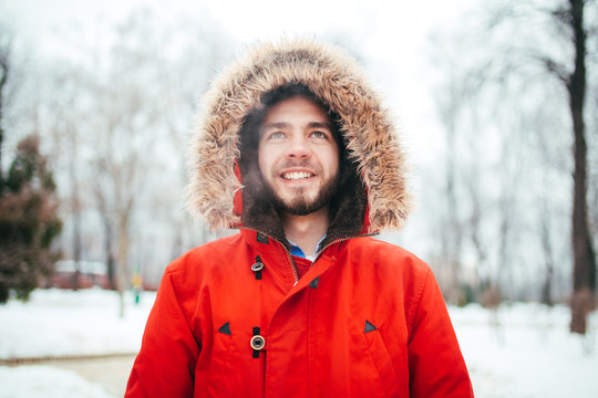 Portrait, close-up of a young stylishly dressed man smiling with a beard dressed in a red winter jacket with a hood and fur on his head. Winter and frost theme.