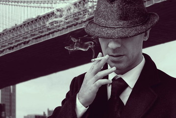 vintage elegant mafia gangster walking under new york bridge