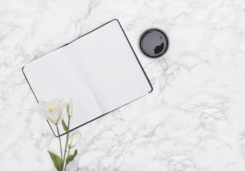 Open notebook, black coffee and white flowers laying on marble desk. Copy space. Flat lay.