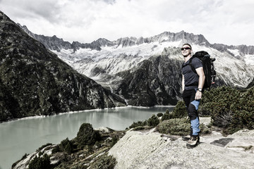 Hiker enjoys the breathtaking view of a mountain lake in the Swiss Alps