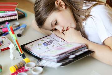 Beautiful preteen girl daydreaming with her head lying on hands looking at her romantic diary. Close-up