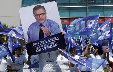 A supporter holds up a poster of the National Integration Party (PIN) presidential candidate Juan Diego Castro, during a campaign rally in San Jose