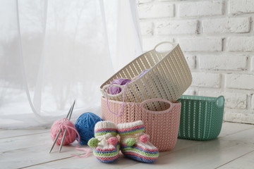 Knitten things and needlework accessories in home organizers colored baskets