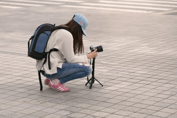 Girl with a backpack, camera and tripod