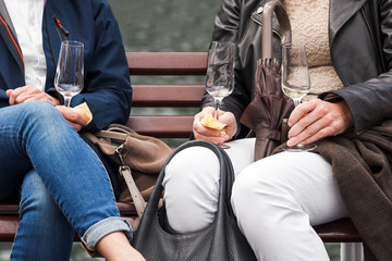 Two Women Drinking White Wine Sitting on a bench