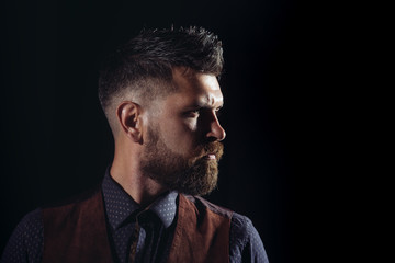 Side view portrait of confident bearded man with beautiful hairstyle. Side view portrait of thinking stylish young man. Handsome bearded young man isolated on black background.