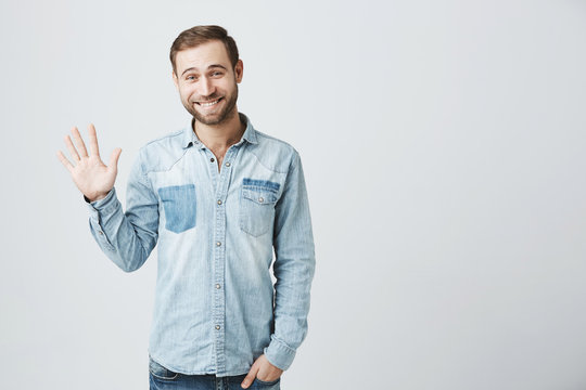 Friendly positive smiling young Caucasian man with stubble and dark hair in trendy denim clothes waving with hand, hailing friends while having fun indoors. Human relations and feelings