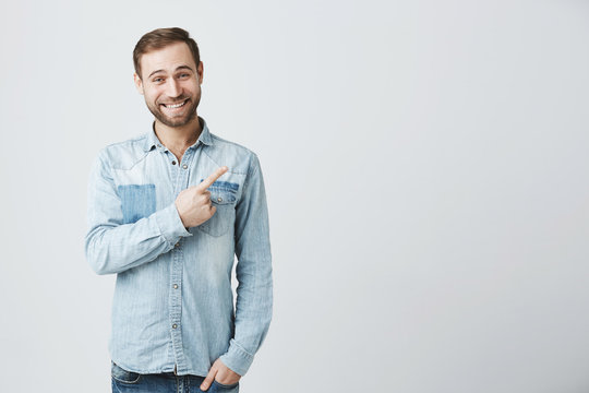 Caucasian young male in denim shirt grins at camera, indicates at copy space, advertises something. Happy bearded man points with fore finger, has satisfied expression, smiles. Look here!