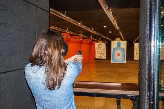 girl shooting gun at range