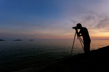 Silhouette of a photographer or traveler using a professional DSLR camera,photographer take sunset photo
