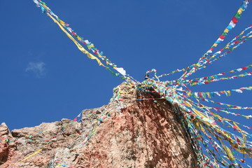 tibetan prayer flags from above with a blue sky background