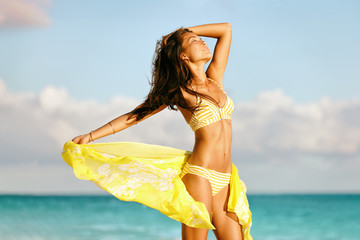 Sexy Asian bikini body model free on beach relaxing with slim legs and toned stomach in yellow swimwear and scarf - cellulite laser treatment , weight loss, wellness concept.
