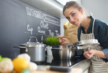 Young woman standing by the stove in the kitchen .