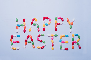 Colorful egg-shaped, sugar coated Easter candy in rainbow colors filled with meringue, chocolate or bubble gum laid out on light blue wooden background saying the words Happy Easter