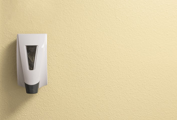 Generic Hand Sanitizer Dispenser on a Textured Cream Wall with Space to Add Writing or Text