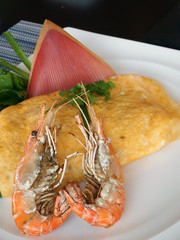 Omelette served with large shrimps with the dish decorated with banana plant