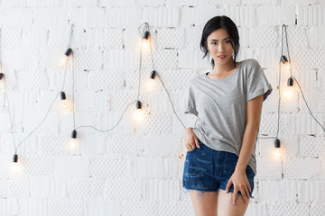 Beautiful young brunette asian model in gray color T-shirt. Portrait of young sexy woman posing at studio and looks at camera. White wall with light bulbs on background.