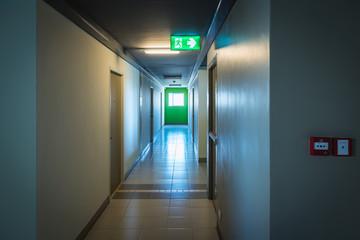 Fire exit sign and fire exit door in building corridor