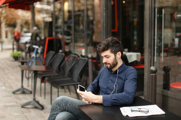 American boy listening to music at cafe with earphones and smart