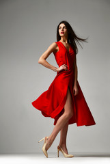 Pretty brunette woman in formal red dress stiletto heels shoes