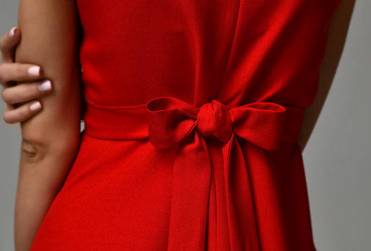 Closeup details of woman red dress bow knot