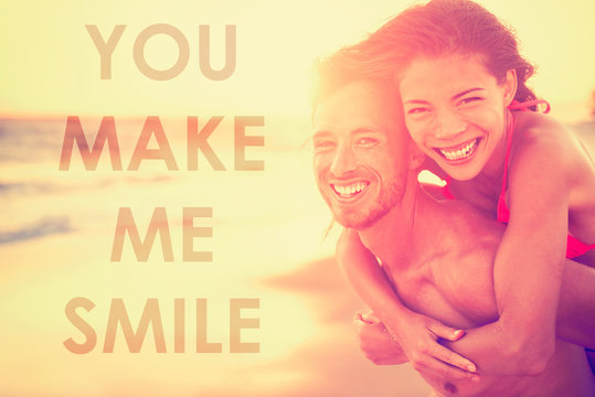 """Happy smiling couple in love with inspirational quote """"YOU MAKE ME SMILE"""" for lovers or valentines day socia media inspiration. Multiracial Asian caucasian couple on beach at sunset laughing."""