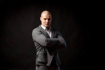 A  bald man businessman  in a white shirt, gray suit confidently looks at the camera and holds his arms crossed on his chest on a black isolated background