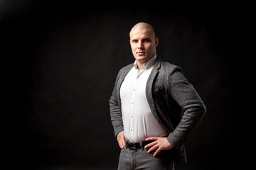 A  bald man businessman  in a white shirt, gray suit  stands in a confident pose, straightening his shoulders on a black isolated background