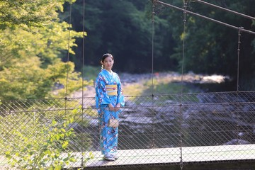 A Japanese girl with traditional Japanese Kimono, standing on a suspension bridge, summer time.
