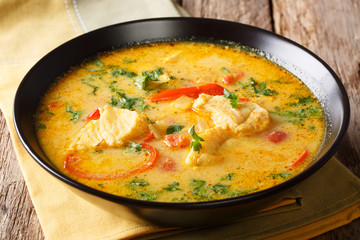 Moqueca stew fish with bell peppers in spicy coconut sauce close-up on a plate. Horizontal